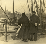 FD-3161 Een dame en een heer kijken vanaf de kade naar beurtvaartbedrijvigheid in de Oudehaven.