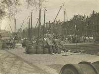 FD-3163 Enkele mannen op tonnen op de kade van (waarschijnlijk) de Oudehaven.,
