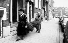 2000-1054-3 Een man en een vrouw dragen een kerstboom naar huis in de Claes de Vrieselaan. Op de achtergrond: het ...