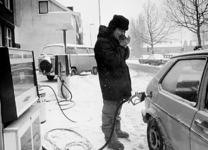 2001-962 Een man met een bontmuts en winterlaarzen aan tankt in de sneeuw bij een Esso pompstation aan de Dordtsestraatweg.
