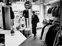 2001-983 Foto van een vrouw in een modezaak tegenover reisbureau Boot & Co op de Meent.