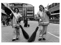 2003-788 2 vrouwen aan het werk op het Beursplein voor het project Rotterdam Schoon van de ROTEB. Zij dragen jassen met ...