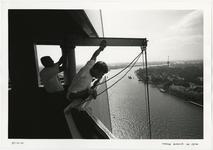 1996-2303 De montage van een tijdelijke buitenlift aan de top van de pyloon van de Erasmusbrug in aanbouw. Op de ...
