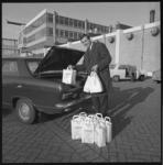 10065 Vertegenwoordiger van de Nederlandse Melkunie demonstreert hoe hij een aantal papieren tassen met yoghurt en ...