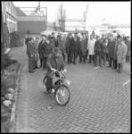10173-1 Een groep mensen kijkt toe hoe man een brommer uitprobeert bij de Berinifabriek van Pluvier-Anker ...
