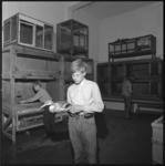 10733 Jongen met een eend in zijn hand in het klaslokaal van Karel Schot in de Blazoenstraat waar veel vogelkooien staan.