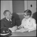 10793 De heer De Korte (links) geeft les aan jongeman in witte brandweerkleding.