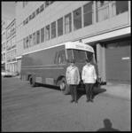 11104-1 Twee brandweerlieden poseren voor een materiaalauto van de brandweer.