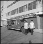 11104-3 Twee brandweerlieden poseren voor een brandweerauto met uitschuifbare ladder.