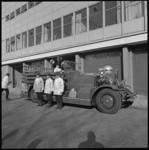 11104-4 Vier brandweerlieden poseren bij de motorbrandspuit Ahrens Fox.