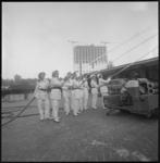 11107 Acht dames in wit bluspak nemen op een binnenterrein aan de Wytemaweg slangen en straalpijpen ter hand tijdens ...