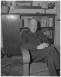 11180 Adjunct-hoofdman 1e klas J. Honig, thuis in een fauteuil.