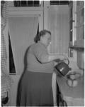 1122-2 In een keuken schenkt een mevrouw vanuit een fluitketeltje water op een filter-koffiepotje.