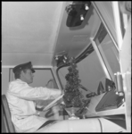 11296 Chauffeur in bluspak zit in brandweerauto met klein kerstboompje naast zijn stuur.