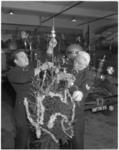 11304 In een brandweerkazerne zijn twee geuniformeerde brandweerlieden bezig een kerstboom op te tuigen; de ...