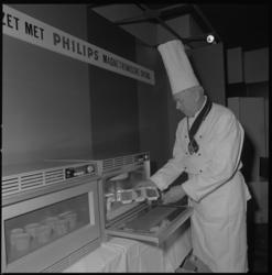 11772 Een kok, met muts op hoofd en onderscheiding om de nek, demonstreert een 'magnetronische oven' van Philips.