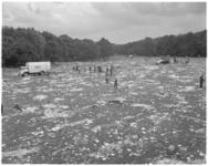 11942 Op een met afval bedekt grasveld in het Kralingse Bos is ROTEB-personeel aan het opruimen.