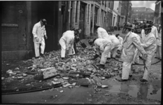20995-5-12 Puinruimende brandweerlieden op de hoek van de Rottestraat (rechts) en de Noorderstraat waar in een ...