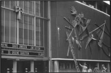 21100-7-4 Een onderhoudsploeg verwijdert de verfbekladding van de gevel van het Thalia Theater aan de Kruiskade 31. Het ...