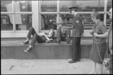 21973-7-33 Politieagent spreekt jongeren aan die voor het Centraal Station liggen.