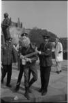22136-5-13 Een lid van de Kabouter-groep wordt door politieagenten weggevoerd; Mariniersmonument op de achtergrond.