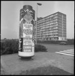 23735-4-2 Reclamezuil met publiciteitsposters; flatgebouw in de achtergrond.