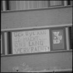 23844-1-6 Politieke leuzen op raam studentenflat omgeving Koningslaan.