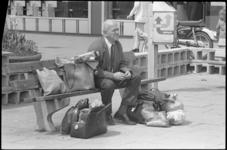 24257-6-23 Man op bankje met aantal boodschappentassen om zich heen.