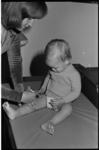 25410-2 Een peuter wordt ingeënt tegen mazelen.