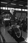 304242-14 Gezeten op een Solex fiets met hulpmotor, opent de echtgenote van minister E.H. Toxopeus, mevrouw H.A. ...