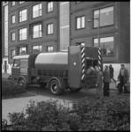 5034 DAF-vuilnisauto met roterende trommel rijdt langs flats terwijl ijzeren vuilnisbakken in de trommel worden geleegd.