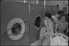 5240-1 Dames aan het werk in de eerste 'Coin Operated Laundry Store' in Nederland, de zogenaamde zelfwasserij, die werd ...
