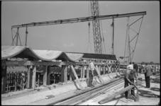 5349 Gewelfde betonnen platen, met een gewicht van zes ton elk, worden door een kraan op het dak van het Caland Lyceum ...