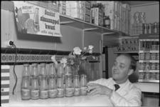 5455 Melkboer Paalvast in zijn winkel met flesjes sinaasappelkwast van Sunkist.