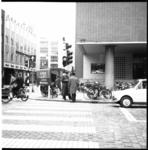 6735 Politieagent deelt bekeuring uit aan voetganger op de hoek Meent-Rodezand. Links het Minervahuis III.