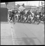 7005-2 Bromfietsers en fietsers onder de omhooggaande slagboom van de Mathenesserbrug. Op de achtergrond het ...