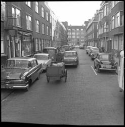 8345 De Heemskerkstraat in de richting van de Bergselaan. Straatbeeld met man op bakfiets, Dafjes en Volkswagenbusjes.
