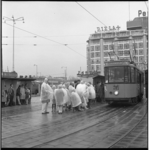 8441 Met regenkleding wachten bij de tramhaltes op Stationsplein; hier tram 16 en rechts het Groothandelsgebouw.