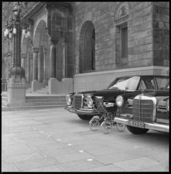 8466 Geparkeerde kinderwagen voor stadhuis tussen de trouwauto's.