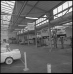8643-4 Monteurs bezig met personenauto's in de autowerkplaats van DAF Schuttevaerweg.