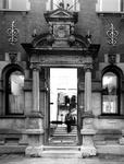 1975-385 Ingang van het Gemeentearchief aan de Mathenesserlaan nummer 315. In het voorportaal staat fotograaf H.M. Vrijmoet.