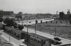 1977-697 De Goudsesingel met op de voorgrond noodwinkels.Rechts de nog onbebouwde Mariniersweg. Op de achtergrond ...