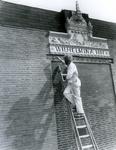 1983-1818 Het opschilderen van het herplaatste gevelstuk, boven het voormalige Wilhelminahof, in een muur aan de Goudseweg.