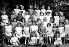 1989-3200 Groepsfoto van meisjes met schooljuffrouw in de tuin van de school voor gewoon lager onderwijs aan de ...