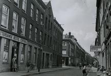 IX-964 De Goudsestraat ter hoogte van de Meermanstraat vanuit het oosten. Op de hoek van de Meermanstraat de apotheek. ...