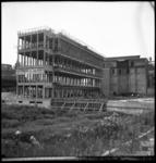 369 Het nieuwe pand van de Gemeentelijke Telefoondienst aan de Botersloot in aanbouw. Op het betonnen geraamte een bord ...