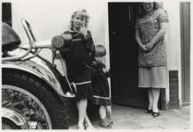 1986-2183 Twee zusjes met dezelfde jurk met hun moeder bij de voordeur van een woning. Uit een serie van 10 foto's over ...
