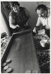 1986-2185 Vrouw en man bij een sjoelbak. Uit een serie van 10 foto's over bewoners van het Witte Dorp.