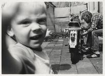 1986-2186 Man sleutelt aan zijn brommer (Zündapp). Op de voorgond een kind. Uit een serie van 10 foto's over bewoners ...