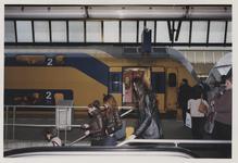 2003-1054-23 Reizigers verlaten een perron van het Centraal Station. Op de achtergrond staat een trein. Uit een serie ...